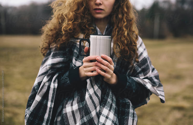 Woman with curly hair, outdoors, with thermos by Aleksandar Novoselski for Stocksy United
