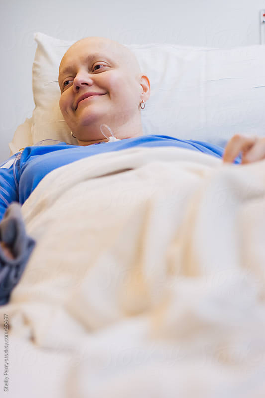 Woman smiles at the hospital for a round of chemotherapy, cancer treatment by Shelly Perry for Stocksy United