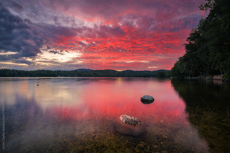 A Firey Pink Sunset On A Lake by Leslie Taylor for Stocksy United