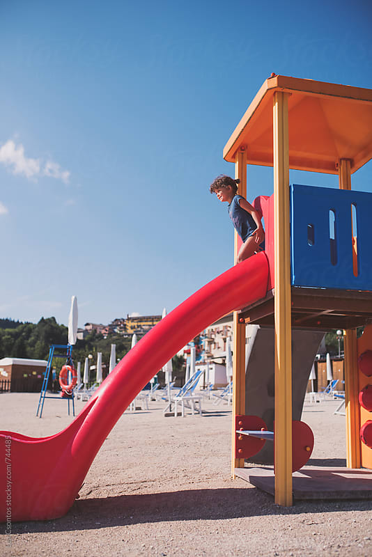Girl on top of a slide on a beach playground by Lea Csontos for Stocksy United