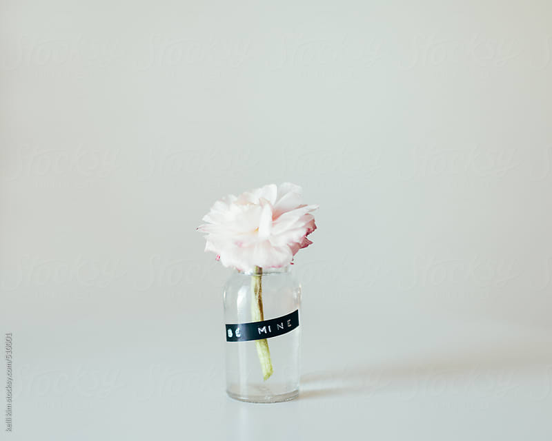 small bottle with pink flower and label Be Mine by kelli kim for Stocksy United