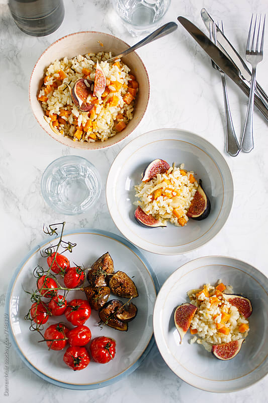 Risotto with sweet potato, figs and tomato meal on a table. by Darren Muir for Stocksy United
