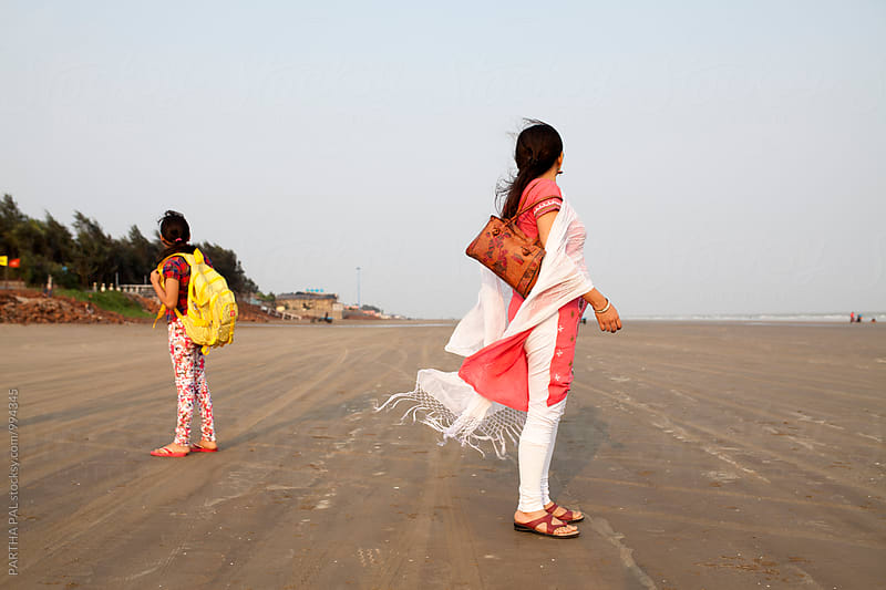 Mother and daughter in a remote beach by PARTHA PAL for Stocksy United