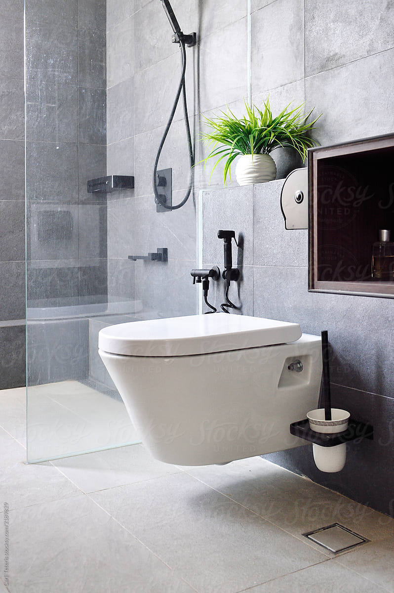 Contemporary Toilet In A Grey Tiled Washroom | Stocksy United