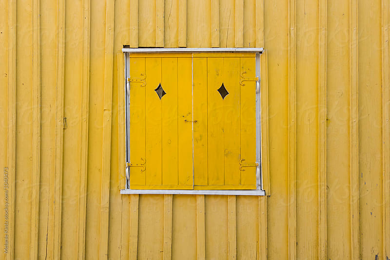 Yellow window with closed shutters by Melanie Kintz for Stocksy United