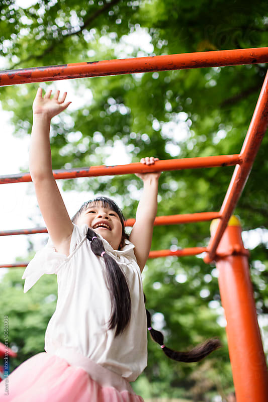 Happy kid hanging on playground by Lawren Lu for Stocksy United
