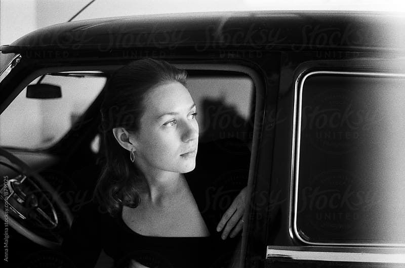 A black and white film portrait of a young woman seating in the retro car by Anna Malgina for Stocksy United