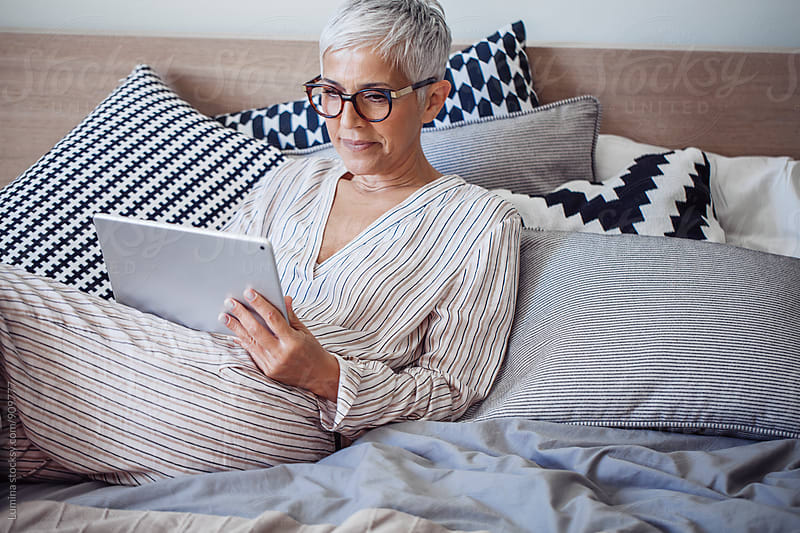 Woman Using a Tablet at Home by Lumina for Stocksy United