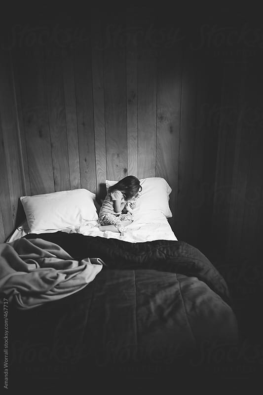 Child hiding face on bed in dark room by Amanda Worrall for Stocksy United