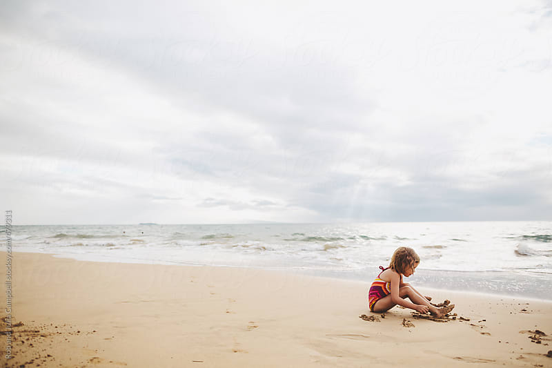Cute little girl playing alone in sand on tropical beach by Rob and Julia Campbell for Stocksy United