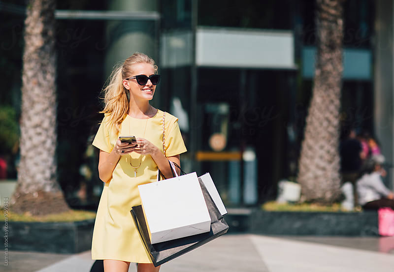 Blonde Woman Carrying Shopping Bags and Texting on the Street by Lumina for Stocksy United