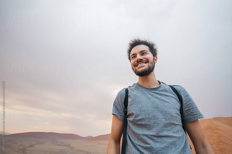 Young happy man with spiky hair because of electrical storm on the desert by Alejandro Moreno de Carlos for Stocksy United