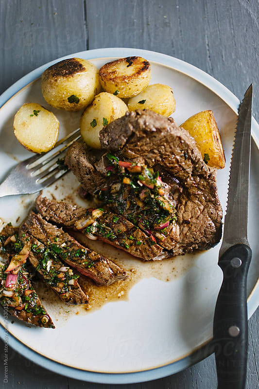 Steak on a plate with chimichurri sauce.  by Darren Muir for Stocksy United