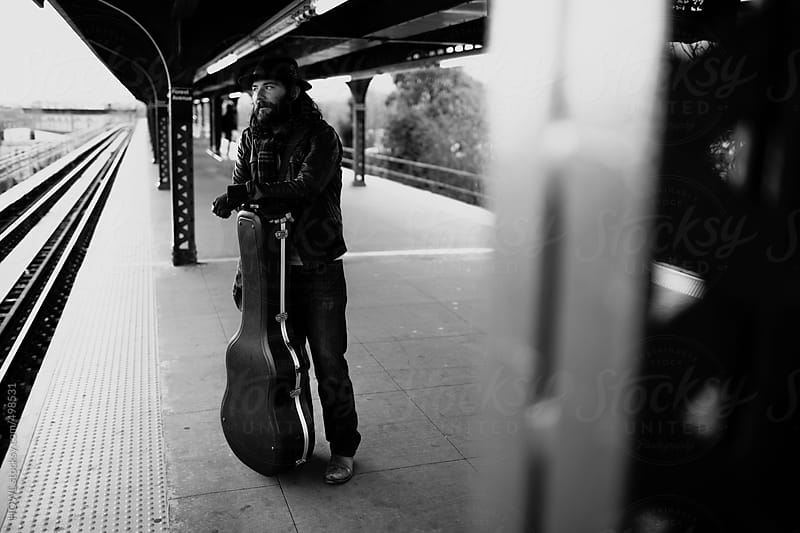 A guitarist stands on a NYC subway platform by HOWL for Stocksy United