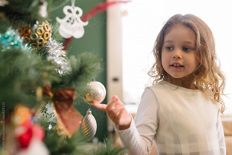 Cute young girl decorating a Christmas Tree by Simone Becchetti for Stocksy United