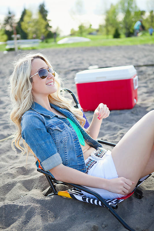 Blonde young woman relaxing in beach chair by Linzy Slusher for Stocksy United