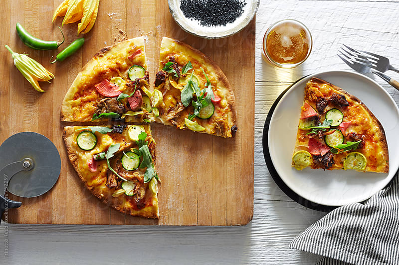 Flat bread with prosciutto, squash and squash blossoms by Trinette Reed for Stocksy United