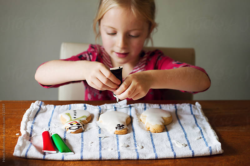 A little girl decorating snowman cookies by Helen Rushbrook for Stocksy United