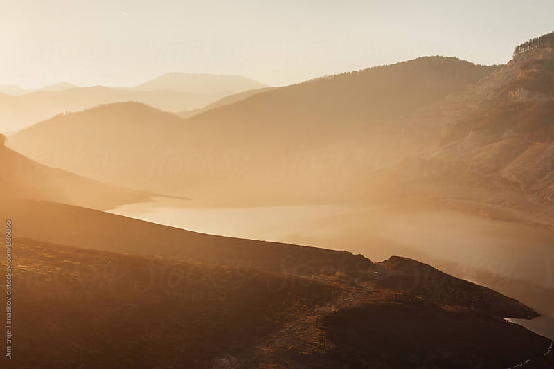 Beautiful sunset above the lake and mountains covered with light fog by Dimitrije Tanaskovic for Stocksy United