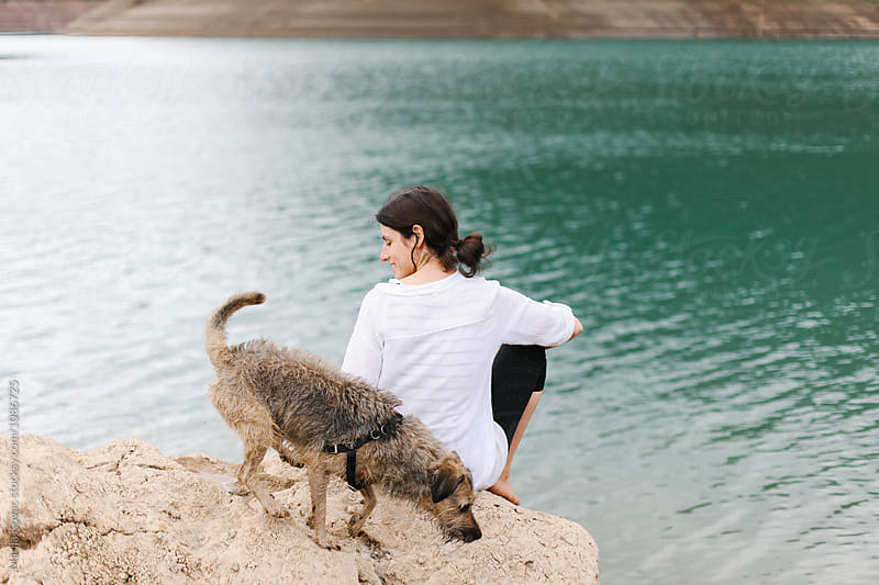 Woman and her dog at the beach by Marija Kovac for Stocksy United