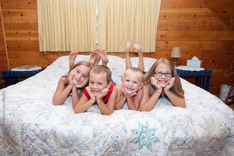 Four siblings on a bed in a wood paneled bedroom by Carleton Photography for Stocksy United