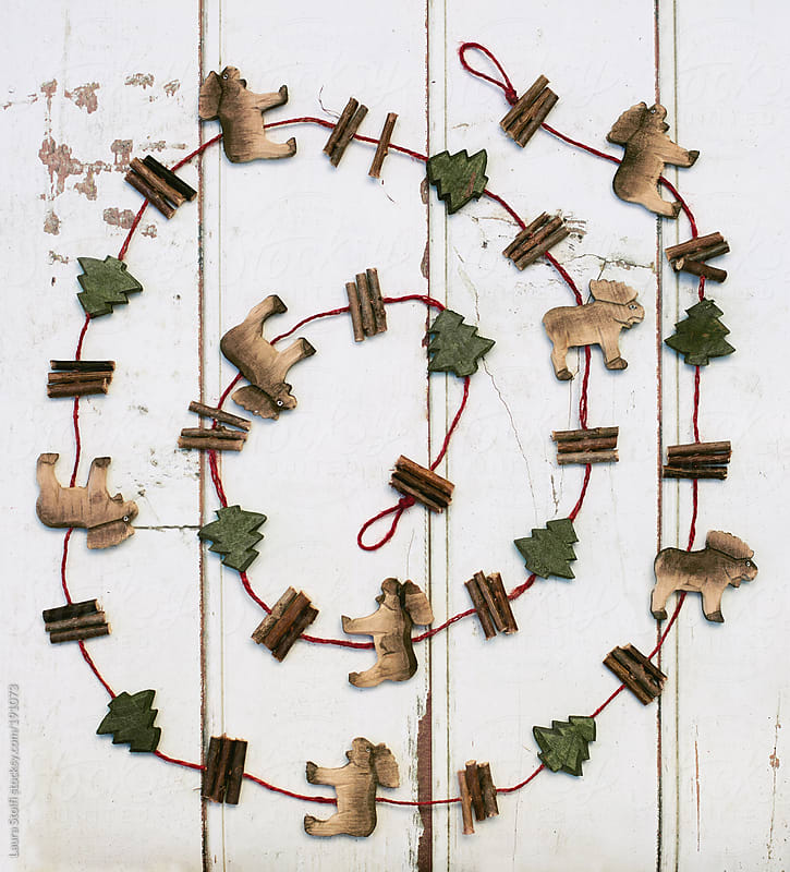 Overhead shot of carved wood garland with reindeers and trees in circle by Laura Stolfi for Stocksy United