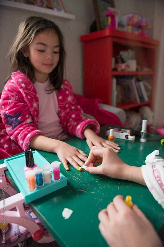 Little Girl Getting Her Nails Done In Her Bedroom by Ronnie Comeau for Stocksy United