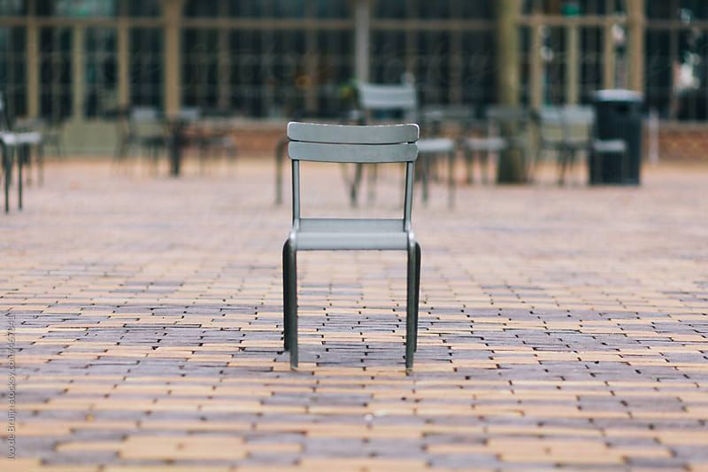 A chair standing alone in a park or square by Ivo de Bruijn for Stocksy United