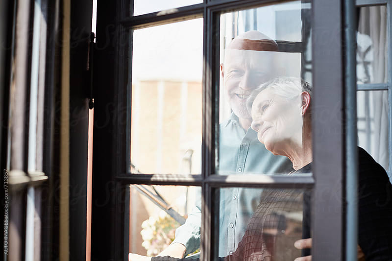 Loving Senior Couple Standing In Doorway by ALTO IMAGES for Stocksy United