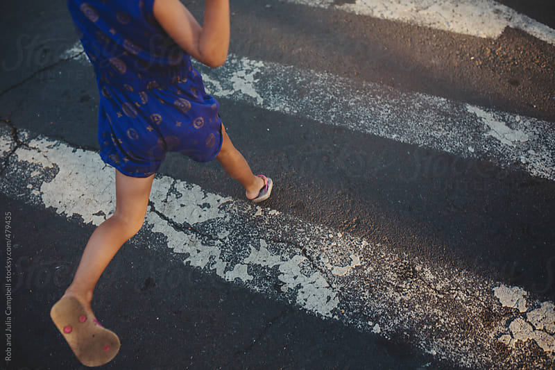 young girls legs running and jumping across crosswalk by Rob and Julia Campbell for Stocksy United