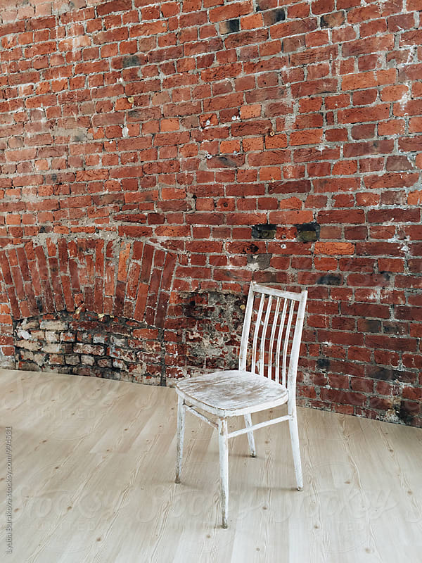Old chair against brick wall by Lyuba Burakova for Stocksy United