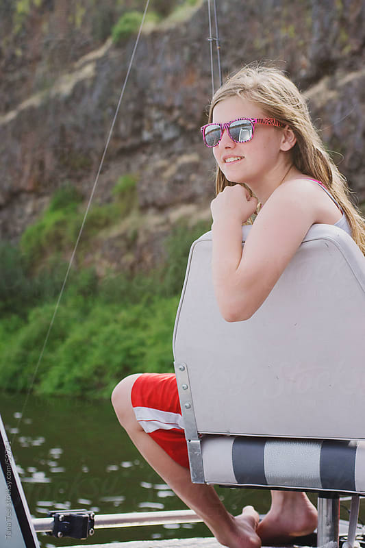 Girl sitting in fishing chair on a boat waiting for fish to bite.  by Tana Teel for Stocksy United