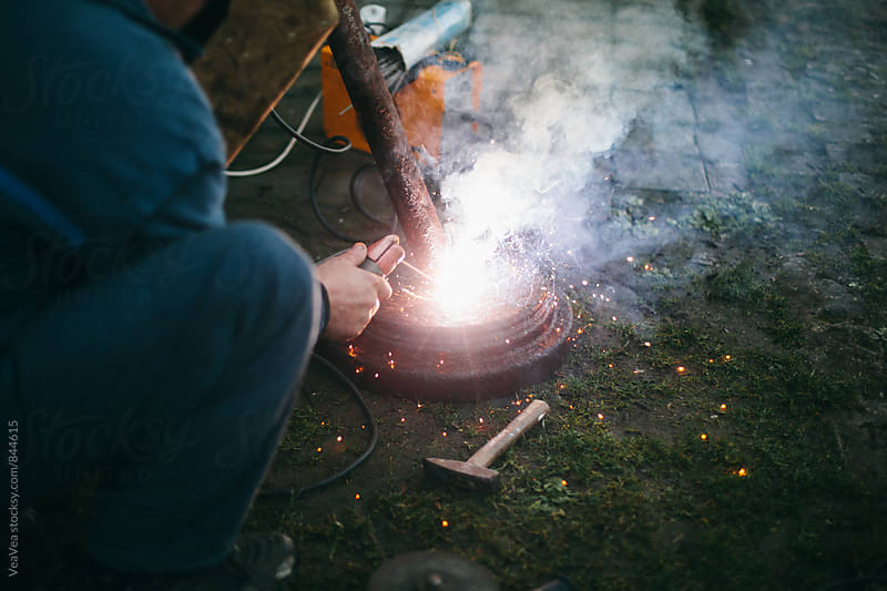 Man welding outdoors during sunset by Marija Mandic for Stocksy United