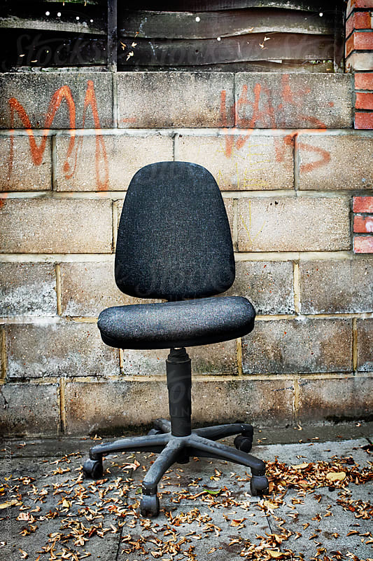 An office chair left by a brick wall by James Ross for Stocksy United