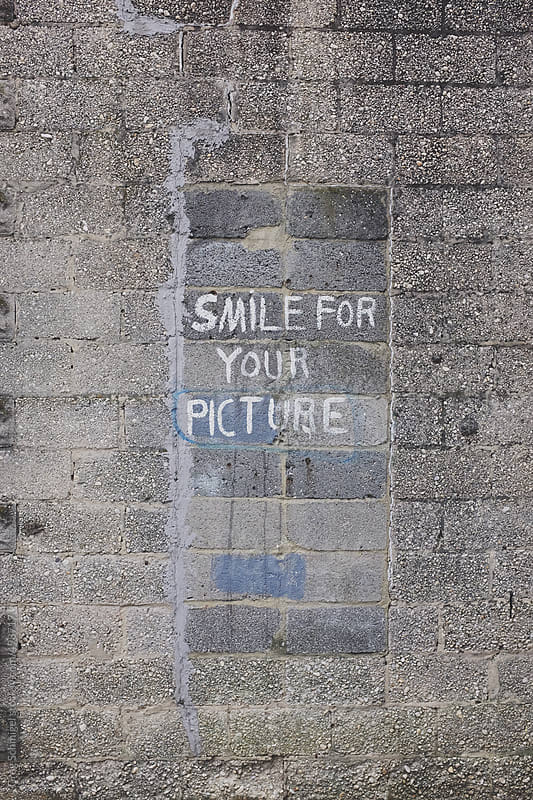 Smile For Your Picture - graffiti on a dirty, grungy gray brick wall in a city by Greg Schmigel for Stocksy United