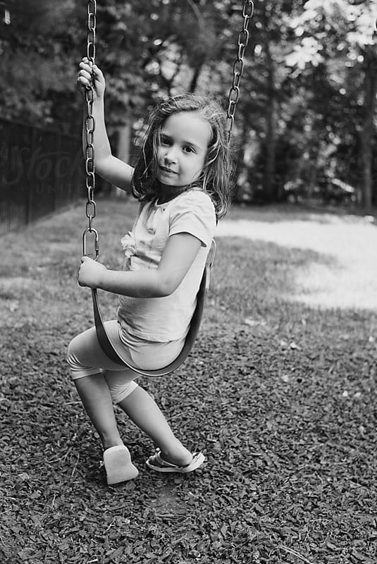 Black and white portrait of a young girl sitting on a swing by Jakob for Stocksy United