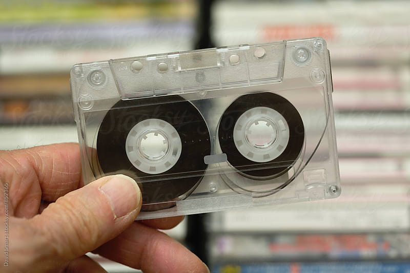 Hand holding cassette tape made of clear plastic by David Smart for Stocksy United