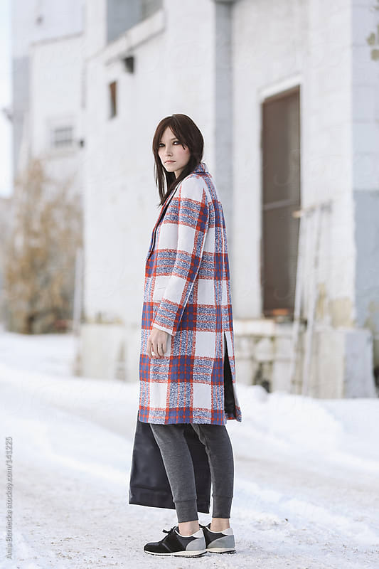 A beautiful woman standing on a snow covered ground looking back  by Ania Boniecka for Stocksy United