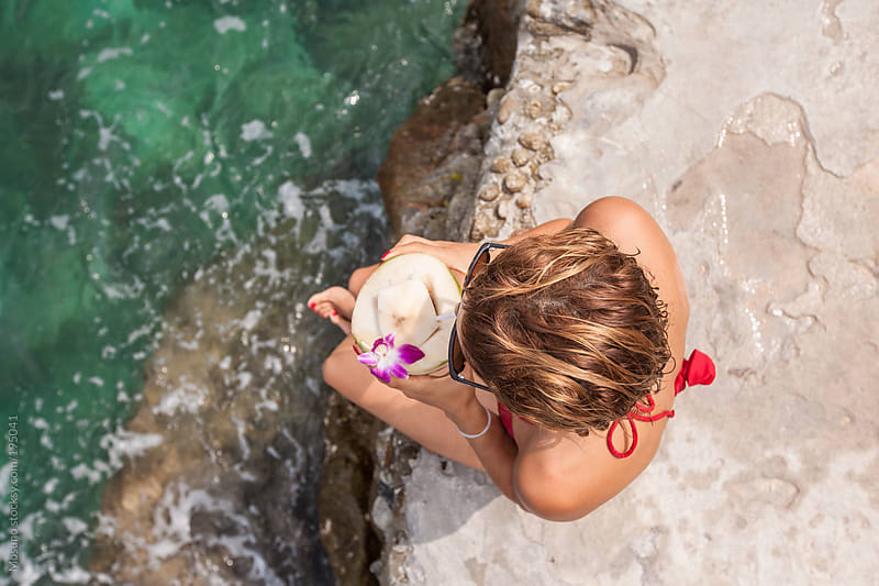 Overhead Shot of a Woman Drinking Coconut by the Sea by Mosuno for Stocksy United