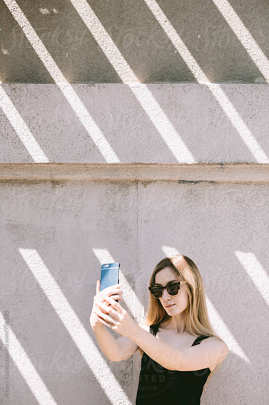 young woman taking a selfie with cell phone by Alexey Kuzma for Stocksy United