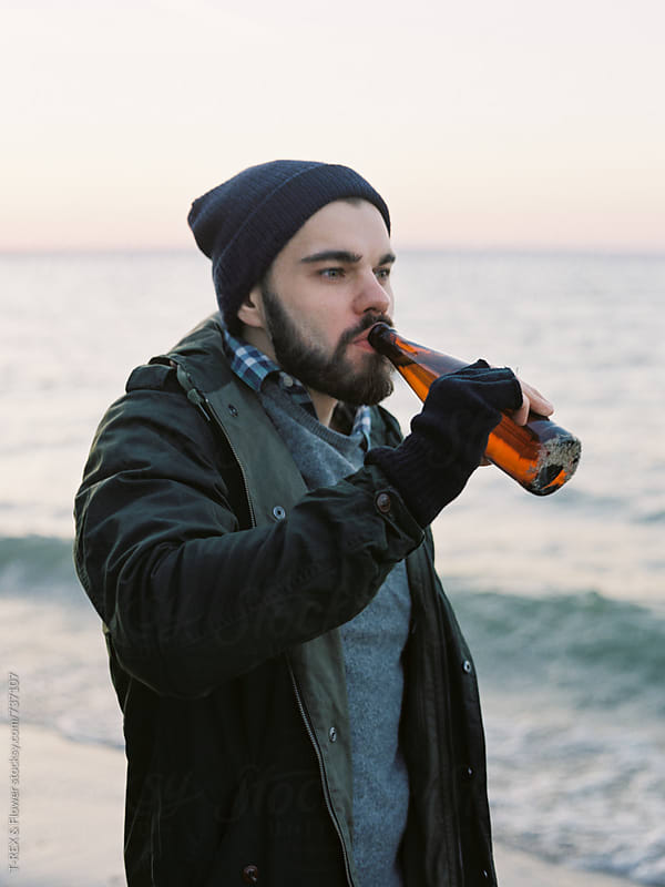 Bearded man drinking beer at the beach by Danil Nevsky for Stocksy United