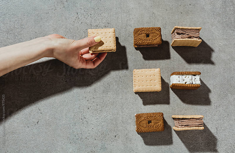 Hand with sanwdich ice cream by Tatjana Zlatkovic for Stocksy United