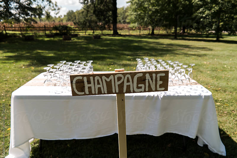Wooden Champagne sign in front of a table by Eddie Pearson for Stocksy United