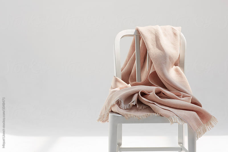 Linen fabric on a metallic chair with white background by Miquel Llonch for Stocksy United