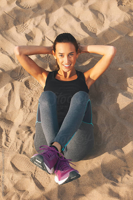 Fitness woman doing abdominals on the beach. by BONNINSTUDIO for Stocksy United