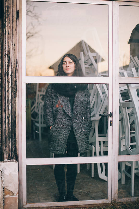 Brunette woman standing behind glass doors by Marija Mandic for Stocksy United
