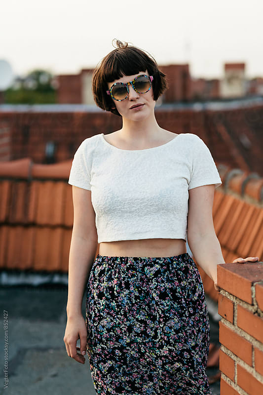 Young woman standing on a rooftop. by VegterFoto for Stocksy United
