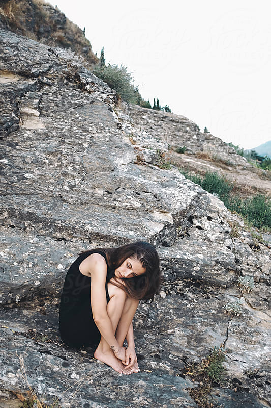 A girl sits alone on a rock