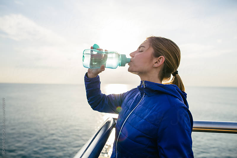 Woman drinking water after running. by BONNINSTUDIO for Stocksy United