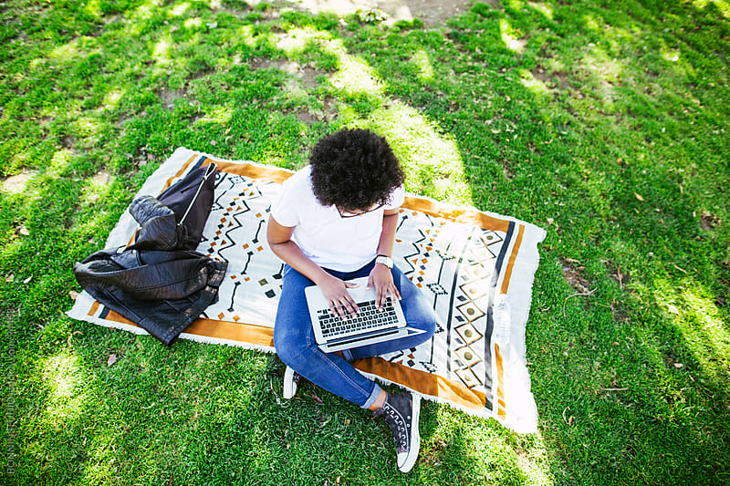 Latin woman working on laptop sitting in the park. by BONNINSTUDIO for Stocksy United
